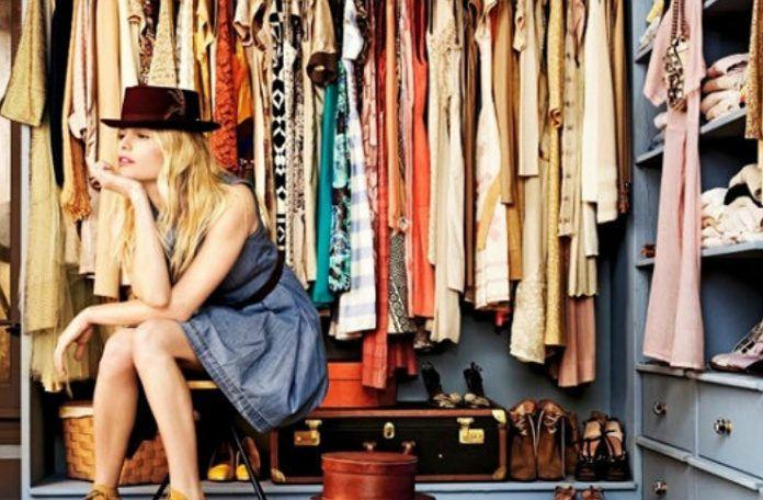 kobieta w niebieskiej sukience i czarnym kapeluszu siedzaca przy garderobie