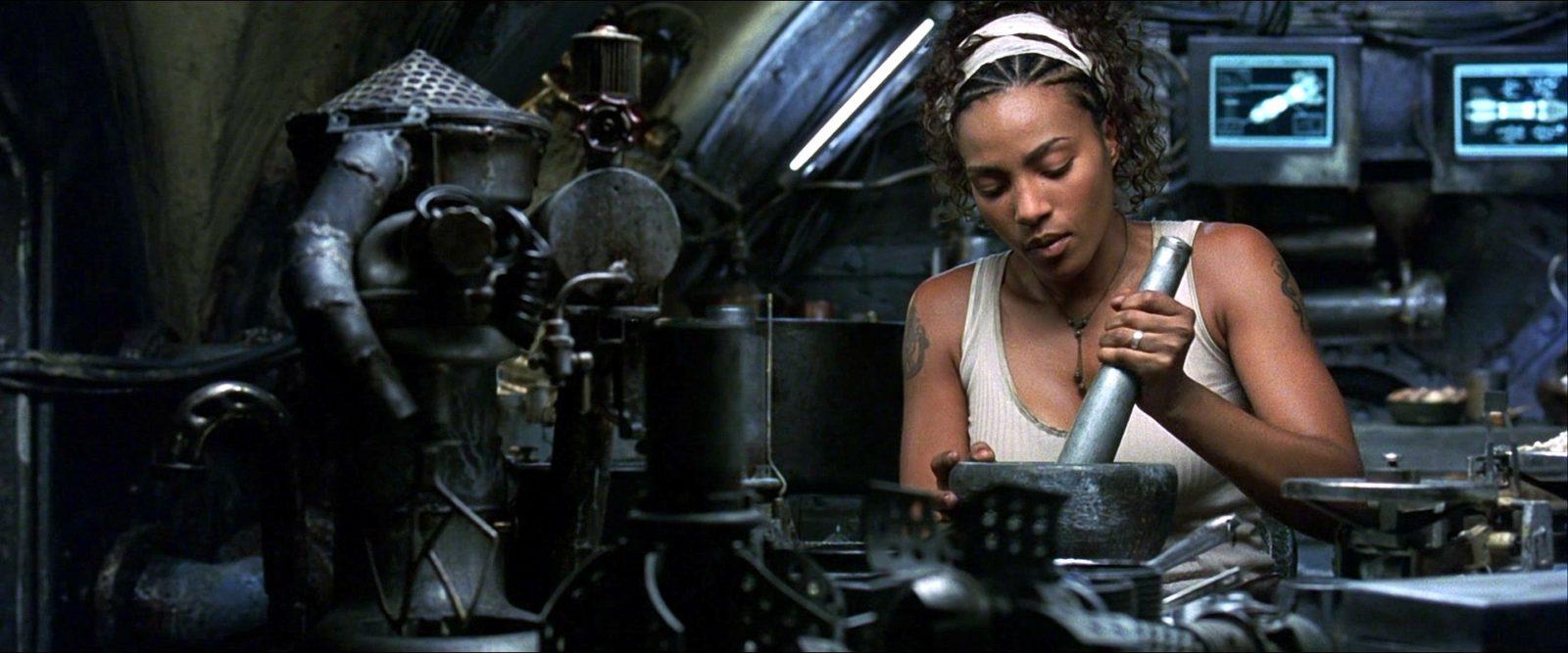 Zdjęcie czarnoskórej kobiety z hutą na splatającą włosy siedzi przy maszynie i konstruuje.