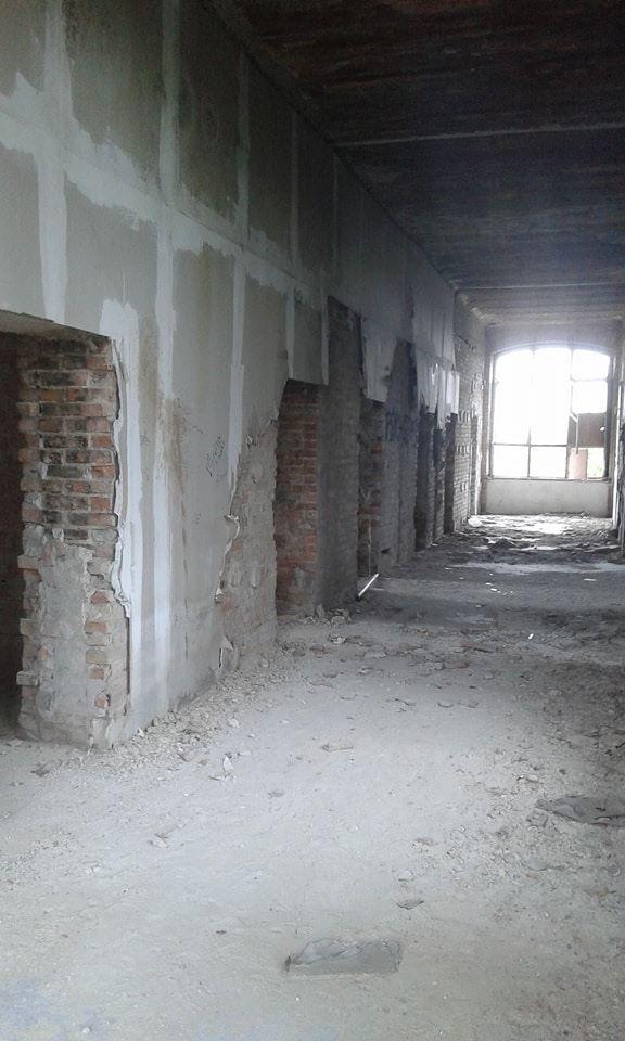 zdjecie korytarza w opuszczonej szkole. widac wejscia do roznych pokoi. Ze scian odpada tynk i widac czerwona cegle