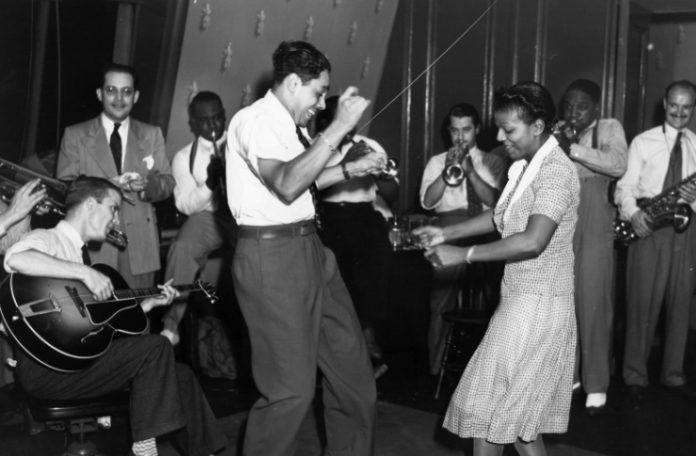 Czarno-białe zdjęcie tańczącej pary. Do okoła nich widać grających na żywych instrumentach muzyków. Kobieta ubrana w wzorzystą sukienkę, mężczyzna w spodnie od garnituru i biała koszulę.