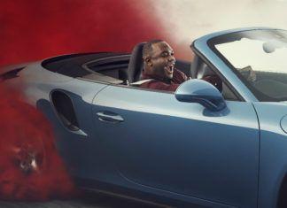 Mężczyzna siedzący w samochodzie za którym unosi się czerwona chmura dymu