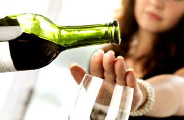Fotografia kolorowa. Kobieta trzyma dłoń nad kieliszkiem, nad jej ręką butelka z winem
