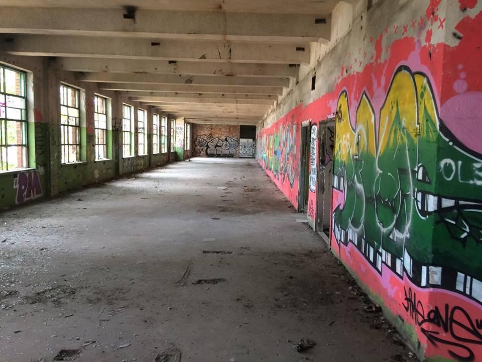 Pomalowana w grafitii ściana budynku Zakładów oraz widoczna duza przestrzen na jednym z pieter. Ponadto rząd kilku okien.