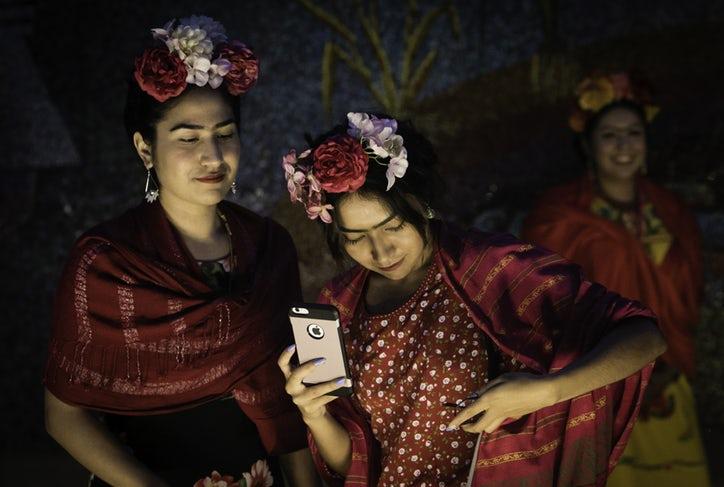 Dwie dziewczyny w czerwonych chustach i kwiatowych wiankach na głowie, jedna z nich trzyma w ręku smartfona