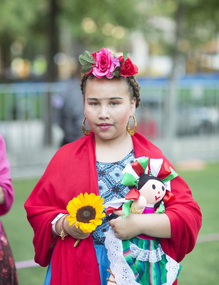 Dziewczyna ze słonecznikiem w dłoni, kwiatowym wiankiem na głowie, czerwoną chustą na ramionach i lalką pod pachą