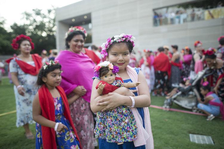 Dziewczynka z wiankiem na głowie trzymająca w ramionach lalkę