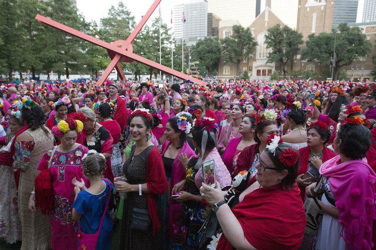 Cieszący się ludzie przebrani za Fridę Kahlo - z wiankami na głowach i różowymi chustami na ramionach