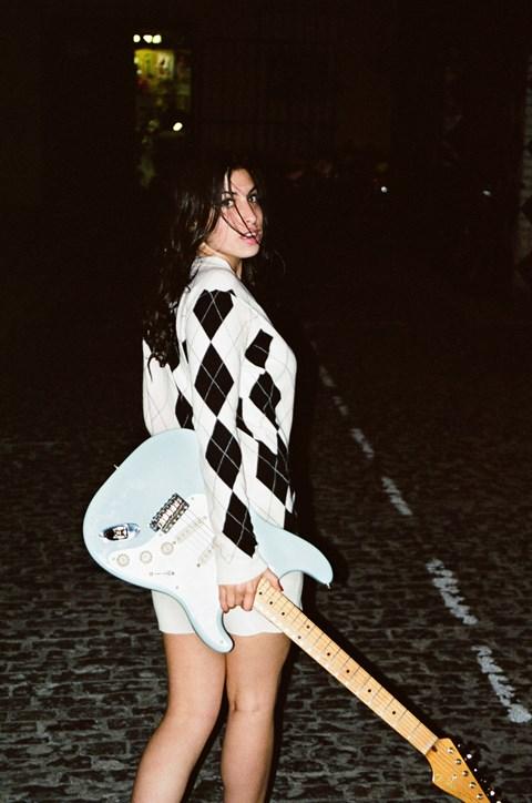 Dziewczyna w sukience w romby, stojąca na ulicy z miętowo-białą gitarą