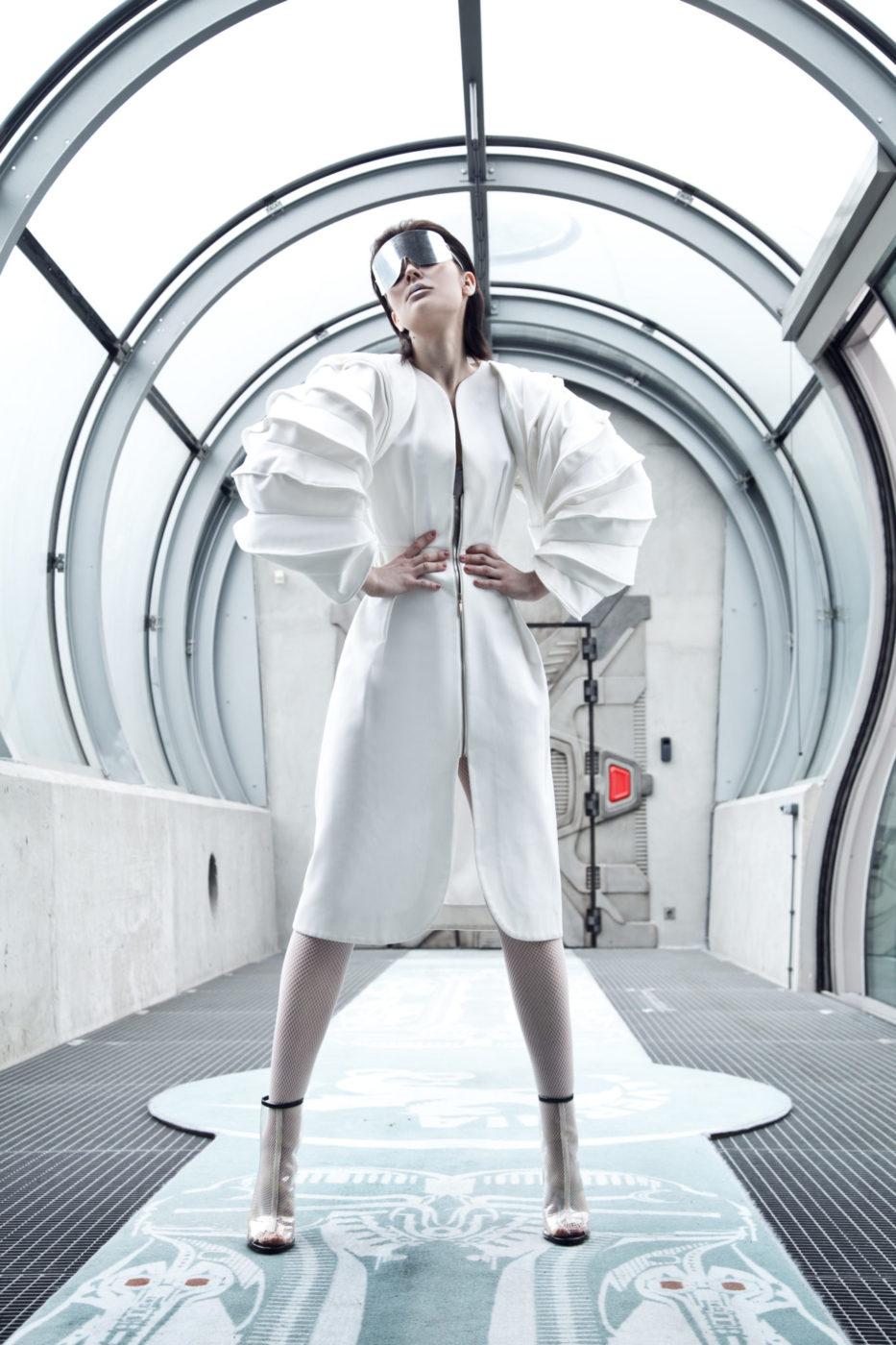 Kobieta ubrana w białą sukienkę z futurystycznymi elementami, stojąca w jasnym korytarzy, na oczach ma duże okulary