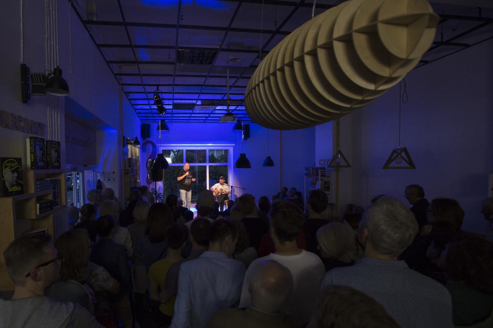 Zaciemnione wnętrze kawiarnii w oddali widać scene z artystami