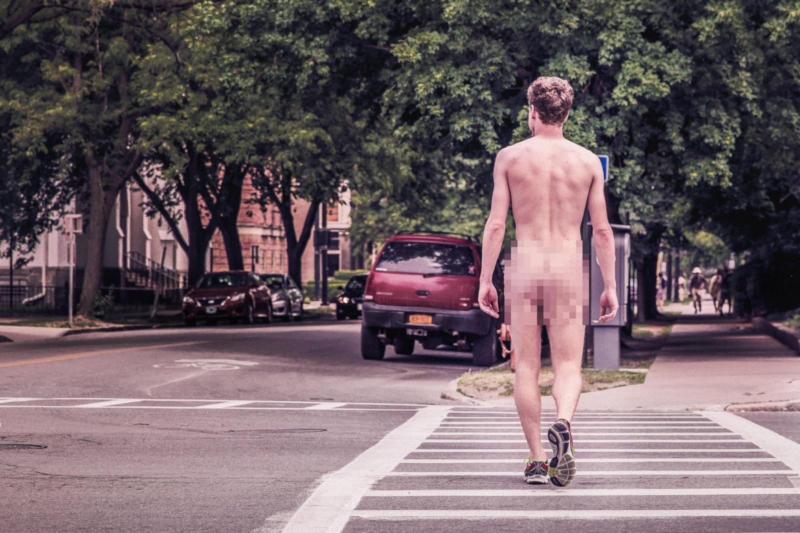 Nagi, biały mężczyzna w samych butach, idzie sobie ulicą. Widzimy go od tyłu,