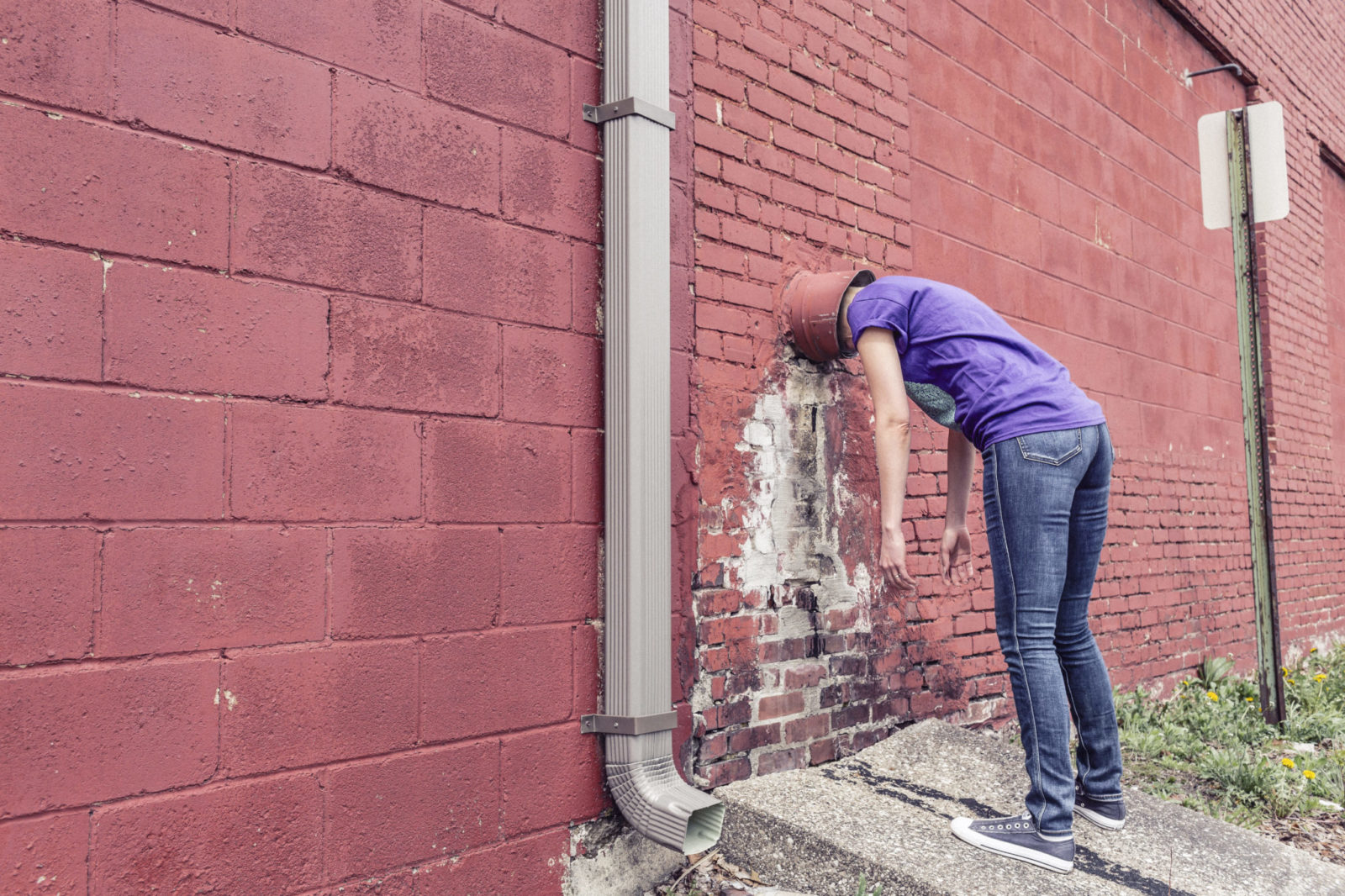 Kobieta w niebieskiej koszulce i dżinsach ma wiadro na głowie i opiera się nim o ścianę z czerwonych cegieł