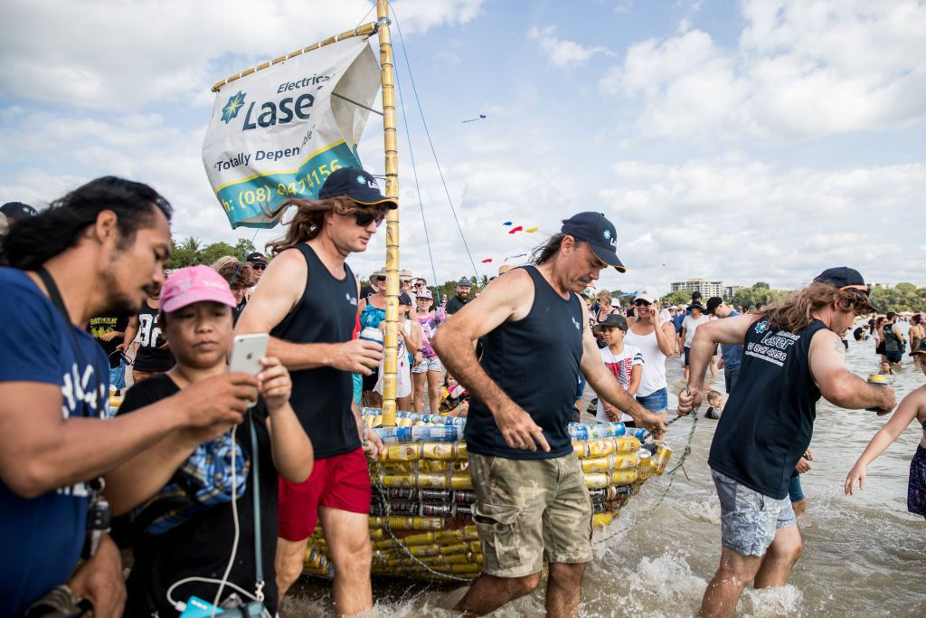 Ludzie stojący w otoczeniu łódek z puszek po piwie