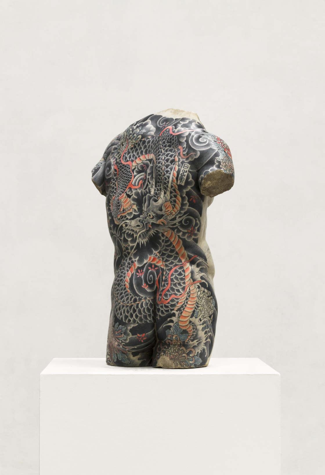 Rzeźba kobiety w ciemnych tatuażach od tyłu