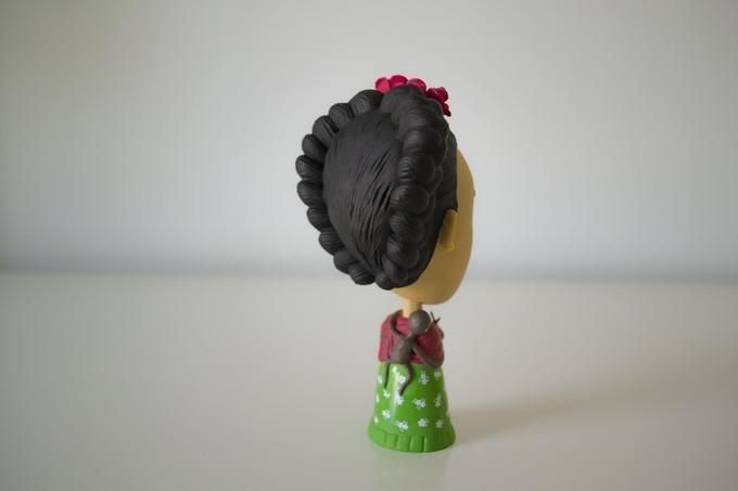 Figurka z plastiku przedstawiająca kobietę z ciemnymi włosami, różami na głowie, w zielonej sukience odwrócona tyłem