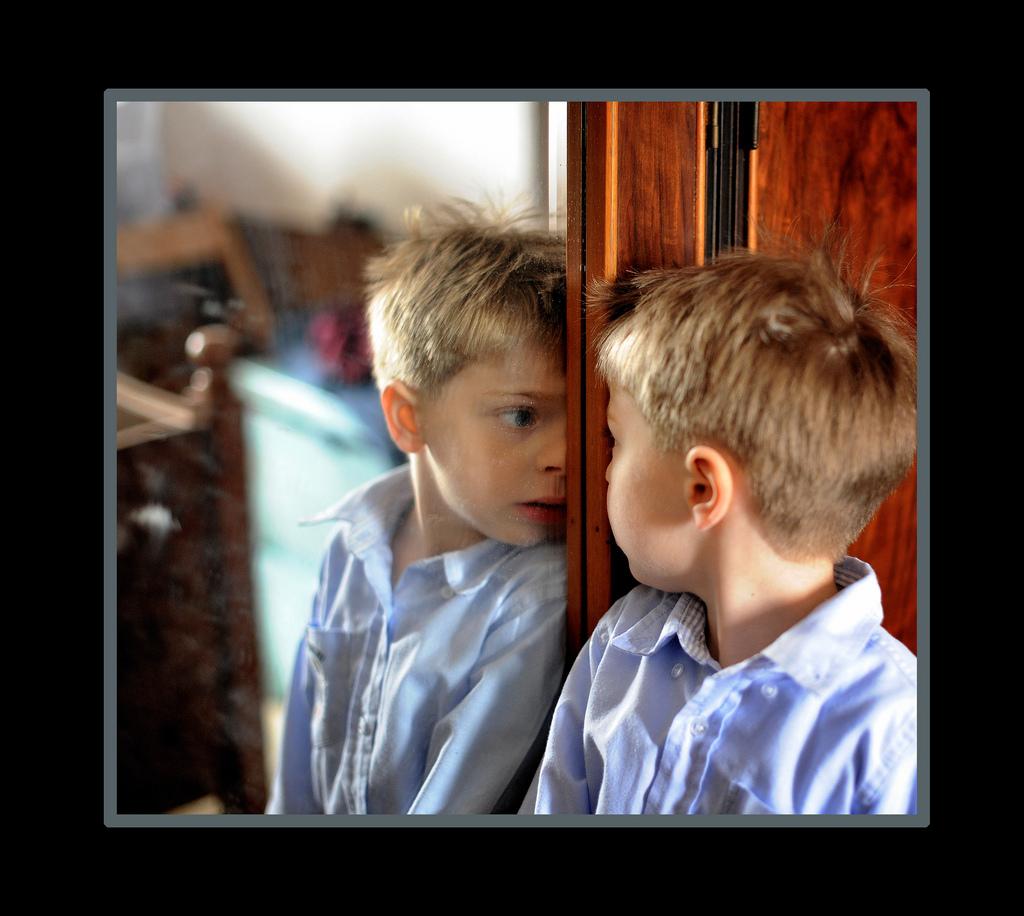 Mały blondwłosy chłopiec patrzący w swoje odbicie w lustrze