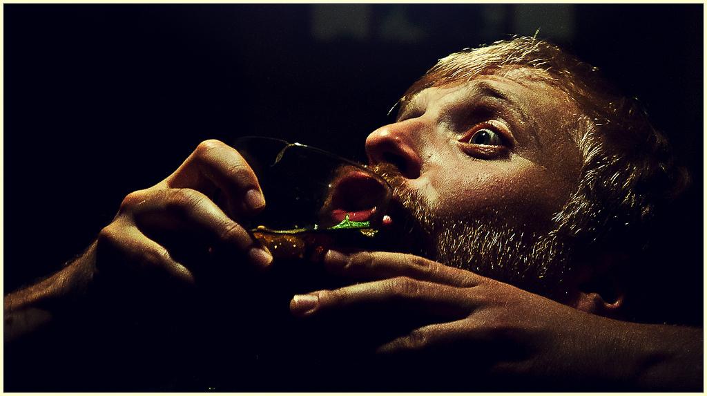 Czarne tło, na którym brodaty człowiek przechyla i wypija szklankę z drinkiem