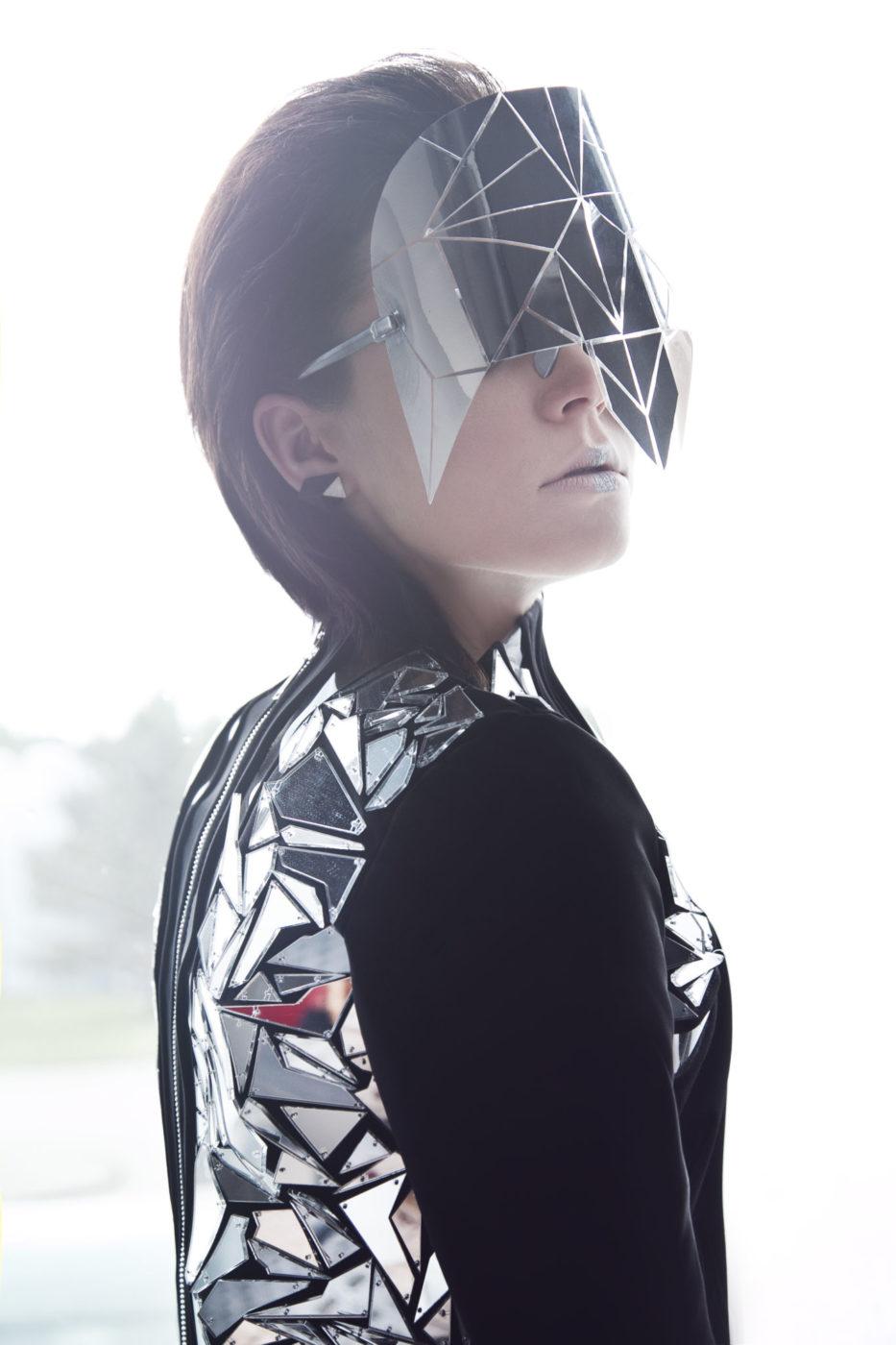 Rudowłosa kobieta ubrana w futurystyczne okulary i sukienkę z lustrzanymi elementami
