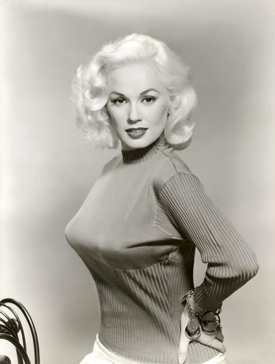 Czarno-białe zdjęcie przedstawiające blondynkę w swetrze