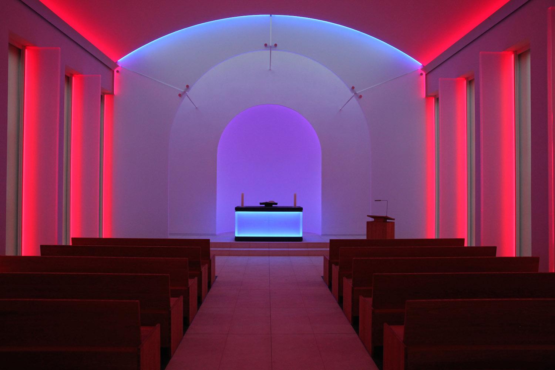 Ołtarz kaplicy oświetlony na czerwono i niebiesko.