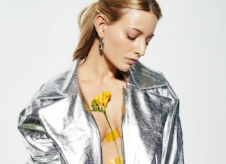 Blondynka z głową skierowaną w dół, z zamknietymi oczami, ubrana w srebrną kurtkę z kwiatami przyczepionymi do klatki piersiowej