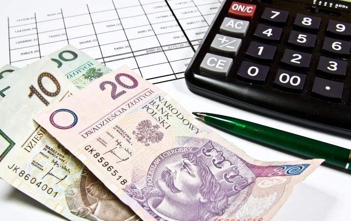 Pieniądze, długopis i kalkulator leżące na wykresie.