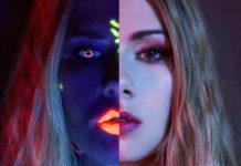Kobieta z dwoma różnymi połówkami twarzy - z jednej strony widzimy ciemną twarz z neonowymi elementami - usta i tęczówki, a z drugiej zwyczajną