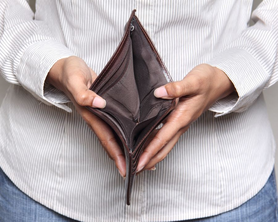 Osoba trzymająca pusty portfel w rękach.