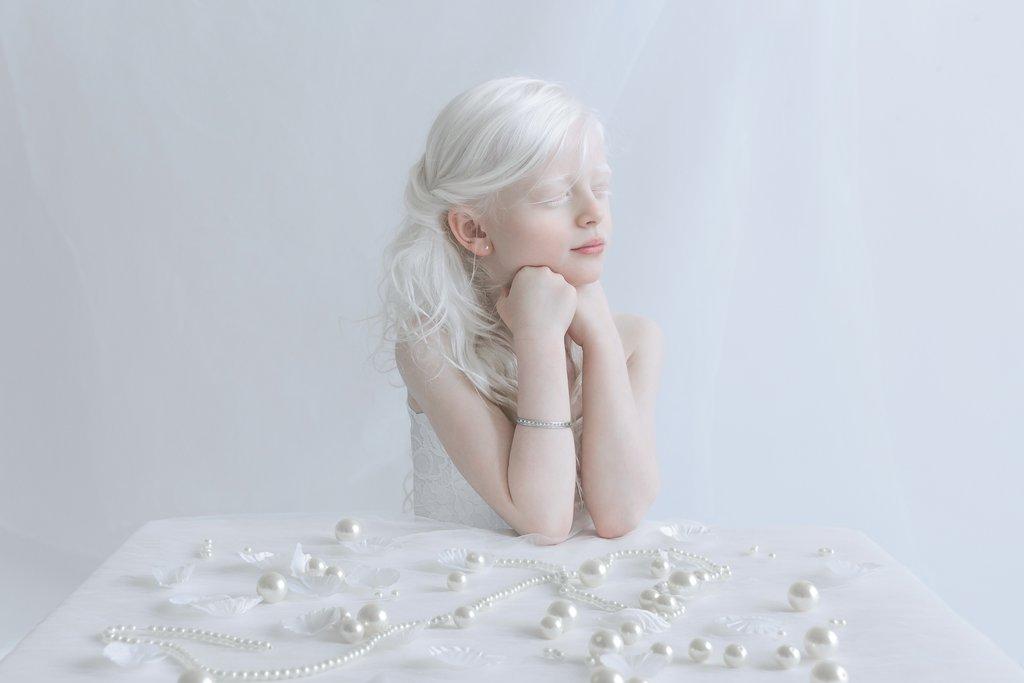 Fotografia kolorowa utrzymana w białych odcienaich. Na zdjęciu widać dziewczynkę-albinos siedzącą przy białym stole, opiera ona ręce o blat, podpierają również brodę. Ma zamknięte oczy. Na blacie rozrzucone są białe perły.