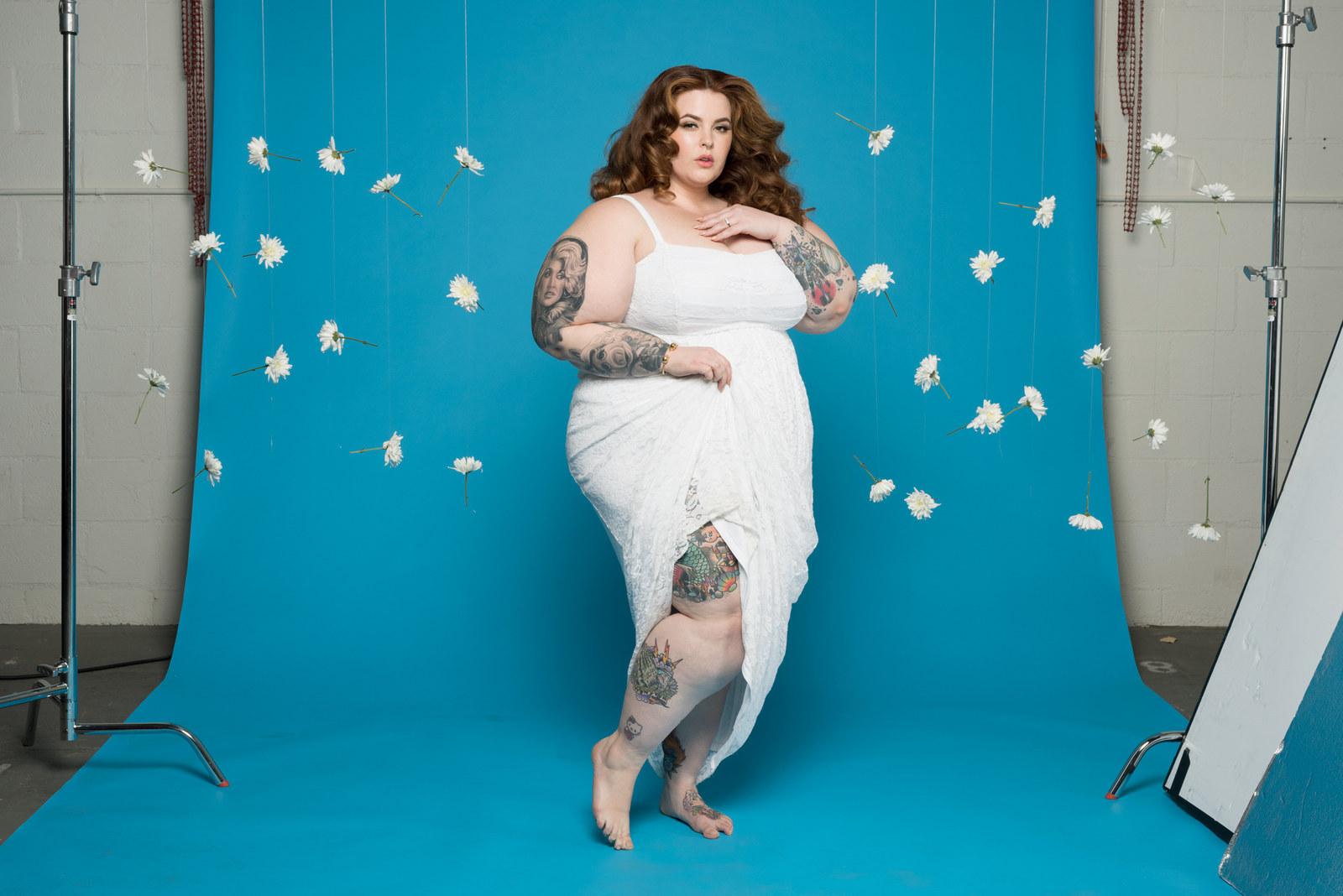 Fotografia kolorowa. Na niebieskim tle, wśród zaiedzonych białych piórek, stoi modelka o pełnych kształtach. Ubrana jest w białą sukienkę na ramiączkach. Ma długie brązowe włosy, zakręcone w fale. Jedną rękę trzyma na brzuchu, a drugą na klatce piersiowej. Na ramionach i nogach widać liczne tatuaże.