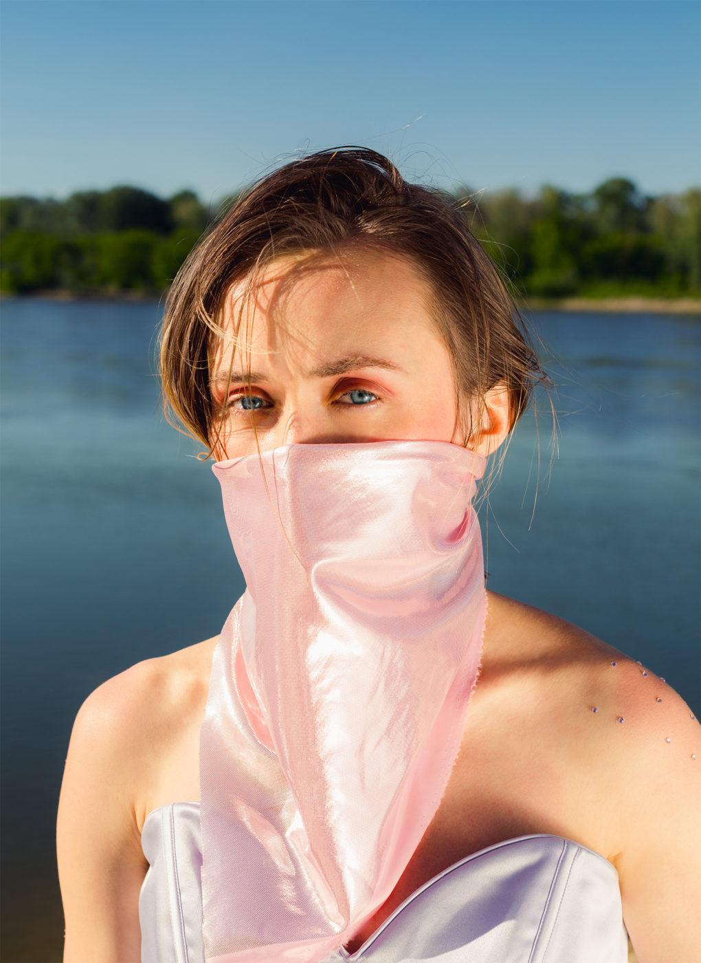 Dziewczyna z różową bandaną na twarzy, zakrywającą nos i usta