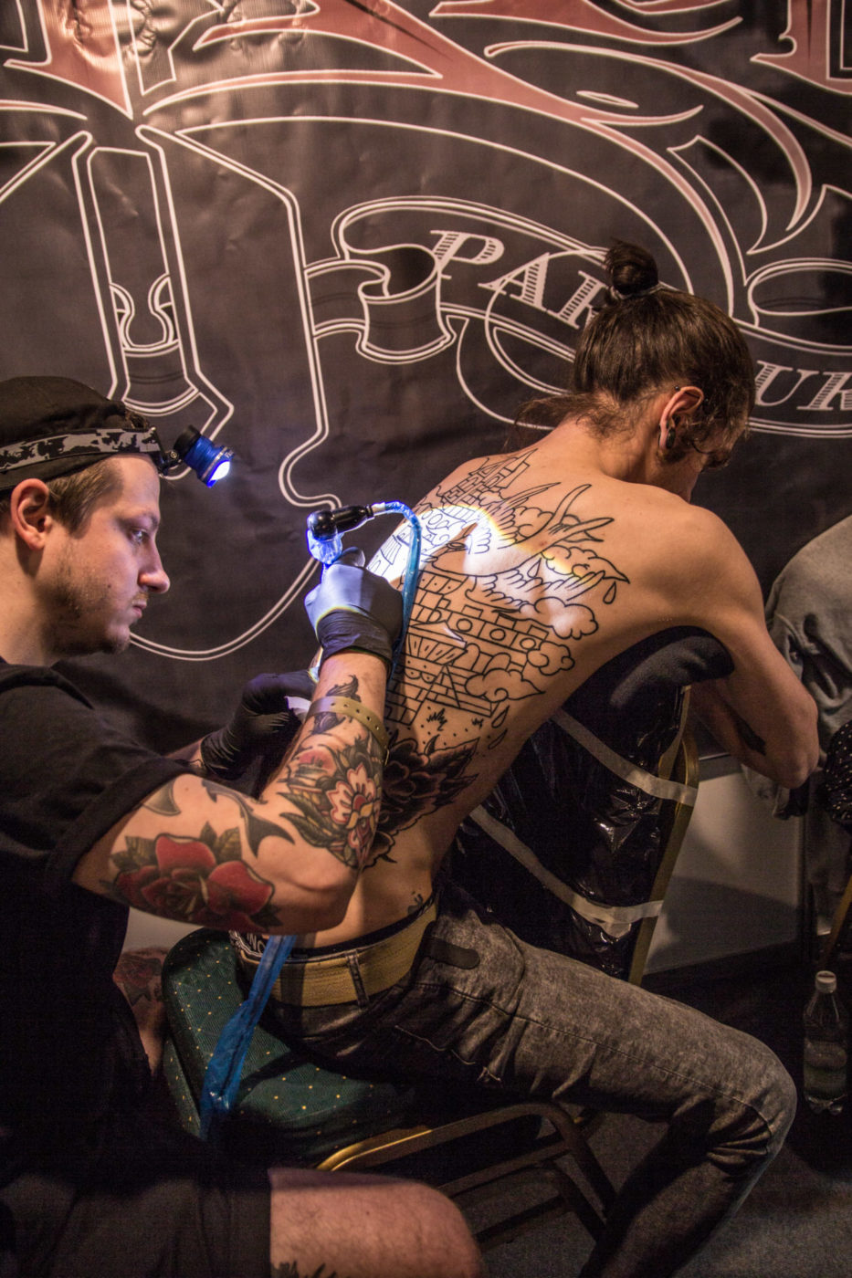Mężcyzna tatuujący plecy mężczyzny