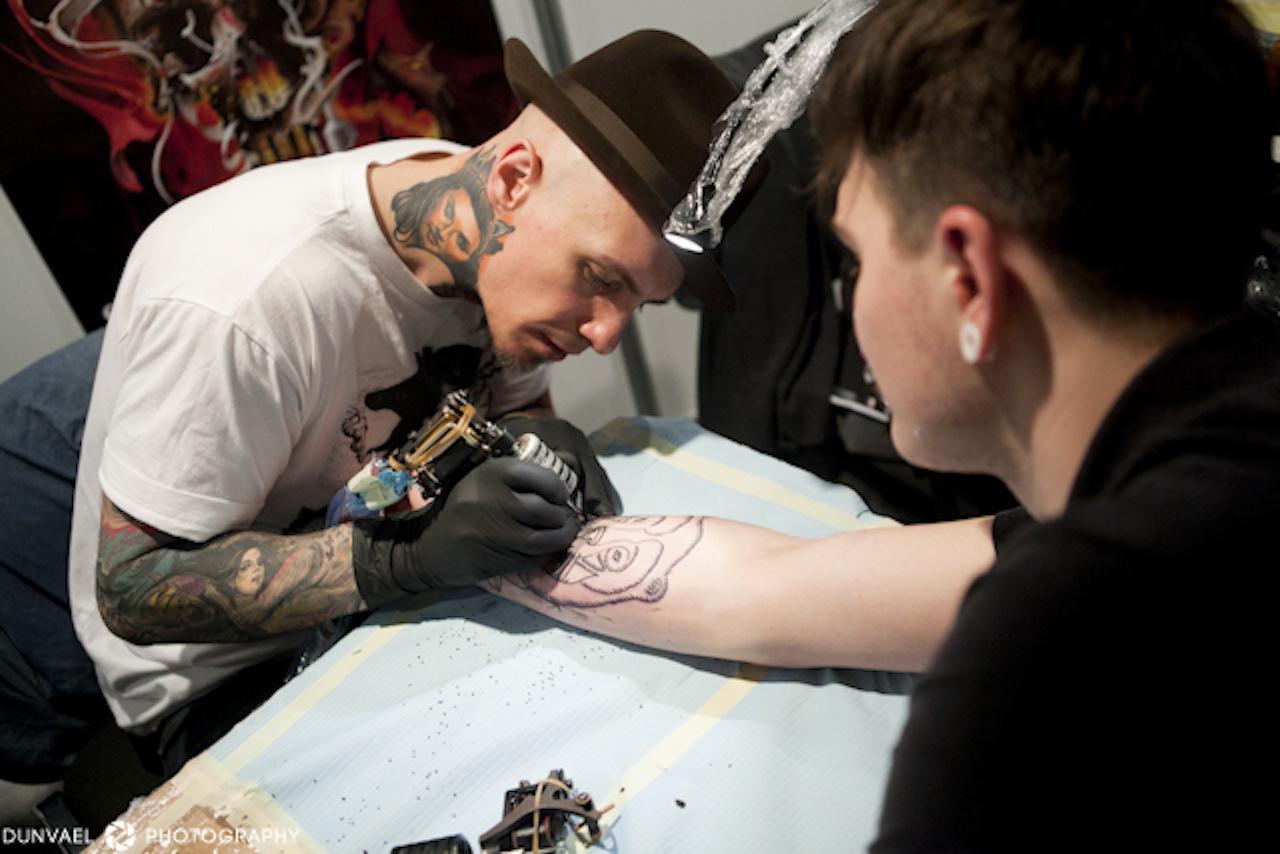 Mężczyzna w kapeluszu tatuujący rękę drugiego męzczyzny