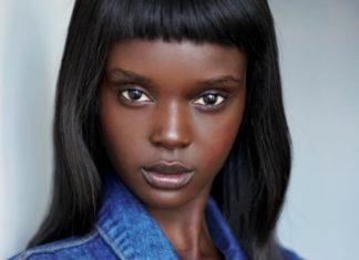 Fotografia kolorowa. Portret czarnoskórej kobiety o długich, prostych czarnych włosach.Kobieta ma grzywkę do połowy czoła. Ubrana jest w niebieską jeansową koszulę.