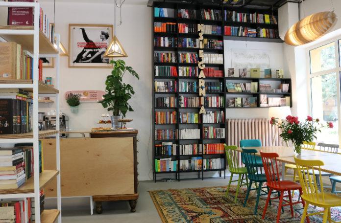 Wnętrze kawiarnii z dużym regałem z książkami i stołem z kolorowymi krzesłami