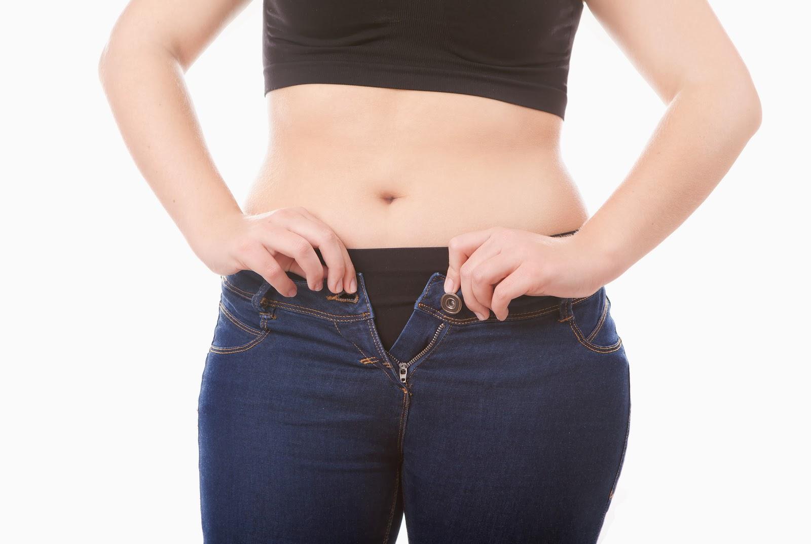 Fotografia kolorowa ukazująca brzuch kobiety. Kobieta ubrana jest w czarny crop top i czarne majtki. Próbuje zapiąc zbyt ciasne niebieskie jeansy.