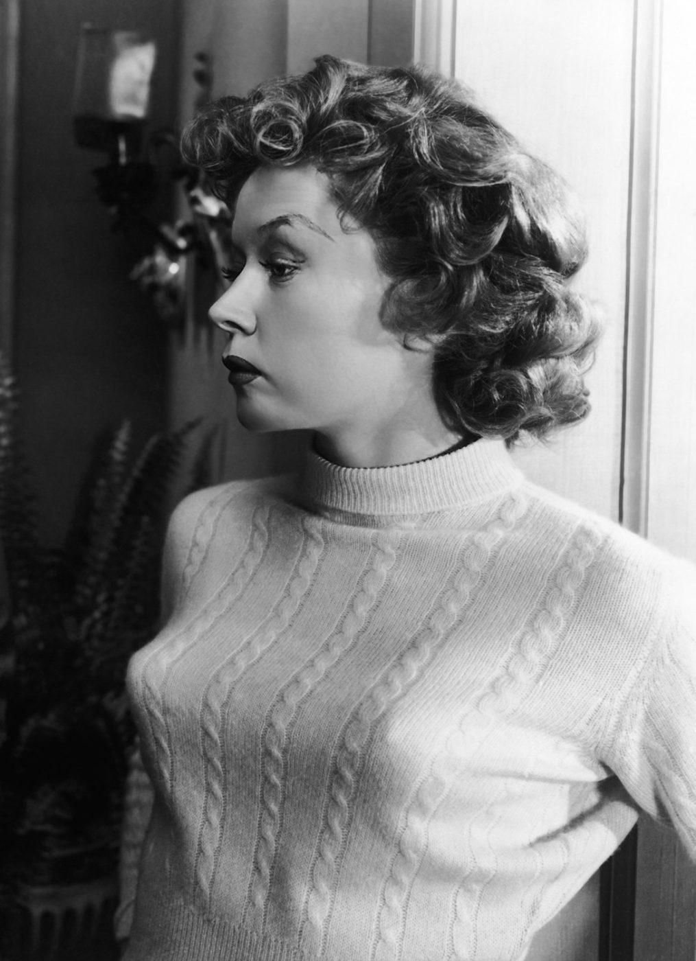 Czarno-biała fotografia portretowa. Na zdjęciu widać kobietę zwróconą profilem. Ma ciemne kręcone włosy. Ubrana jest w jasny półgolf.