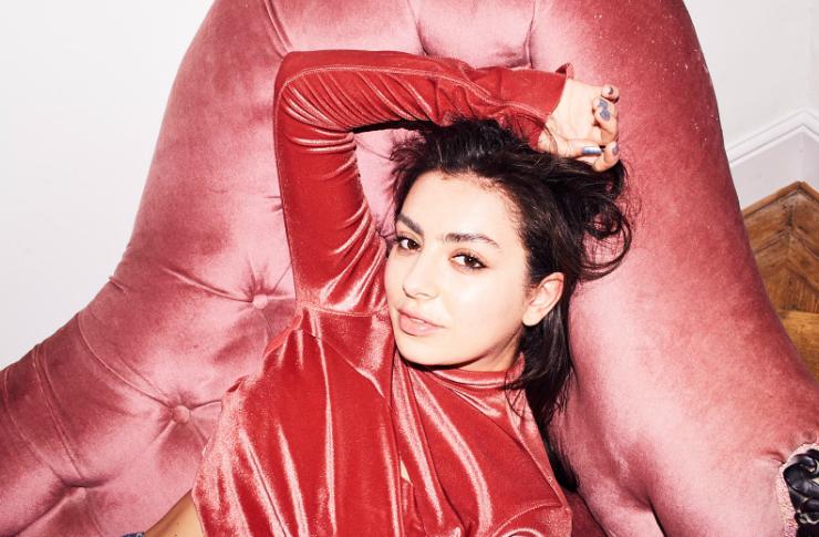 Dziewczyna w czerwonym golfie leżąca na różowym fotelu