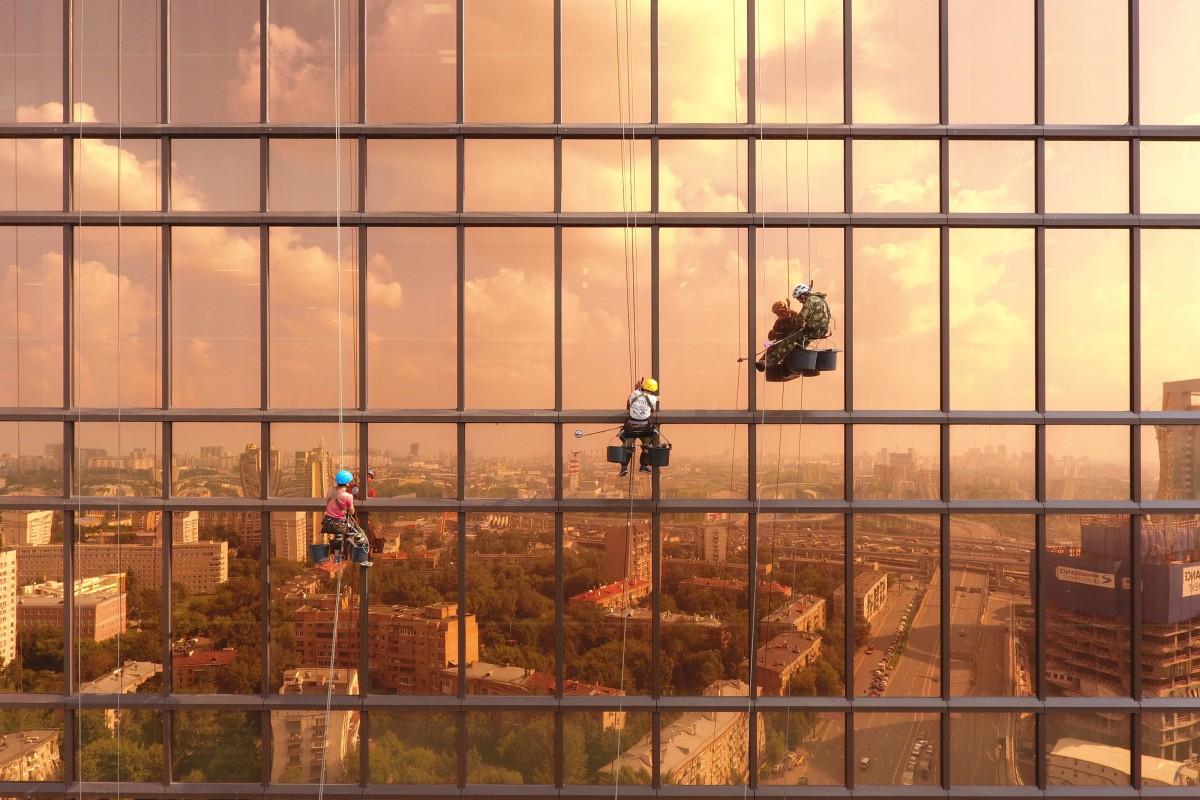 Zdjęcie robione na wysokosci, ktore przedstawia trzech alpinistów myjących szyby wieżowca. W lustrzanych szybach widać panoramę miasta, co razem tworzy mega efekt.
