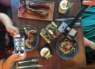 Zdjęcie stołu z góry, kobieta trzymająca smartfon i mężczyzna z selfie stickiem robią zdjęcie posiłku
