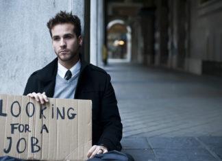 Schludnie ubrany młody człowiek siedzi na pustej ulicy z tabliczką na której napisał ' looking for a job'.