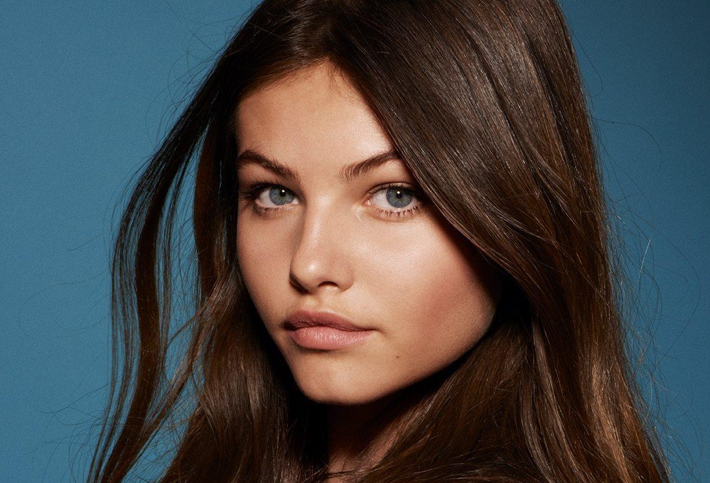 Kolorowa fotografia portretowa. Na zdjęciu widać twarz młodej dziewczyny z długimi brązowymi włosami. Dziewczyna nie ma makijażu. Ma szaro-niebieskie oczy.