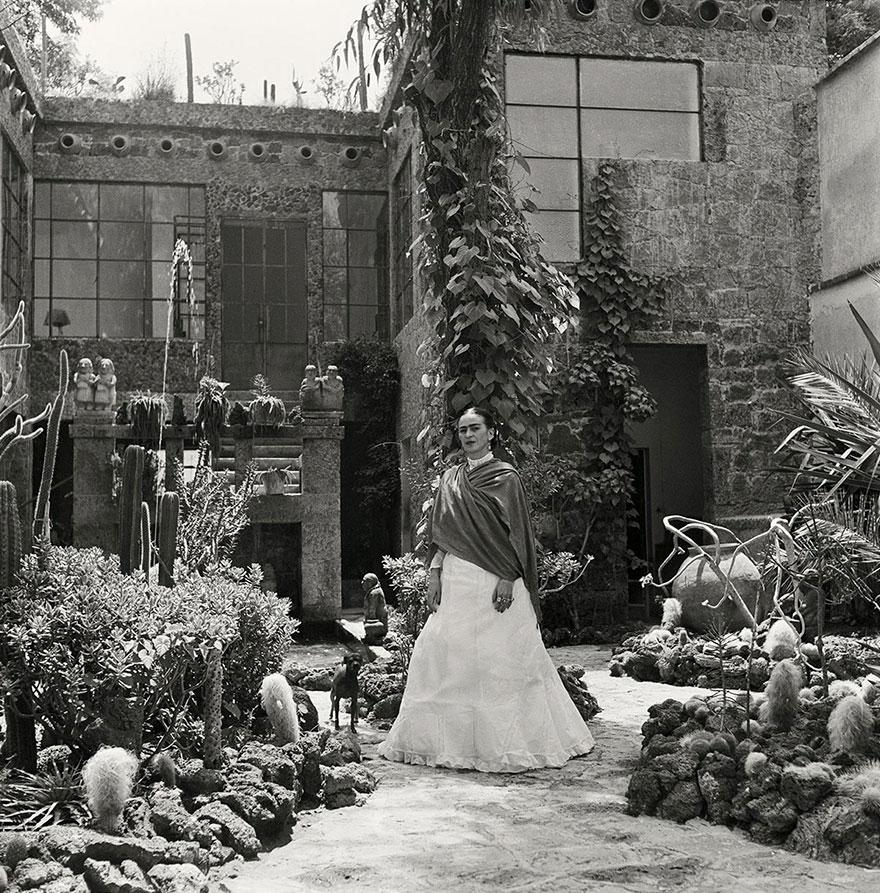 Kobieta w białej spódnicy stojąca w otoczeniu roślin