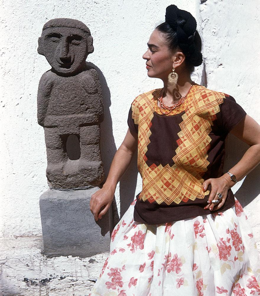 Kolorowe zdjęcie kobiety w pomarańczowej bluzce, białej spódncy, stojacej obok figurki
