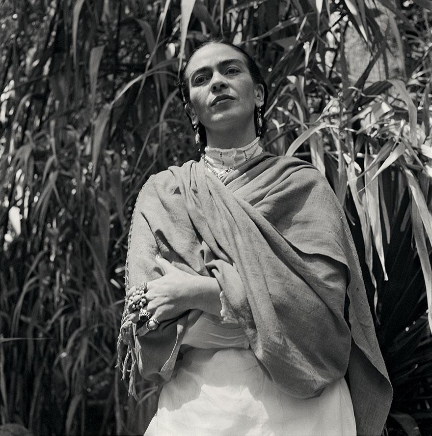 Czarno-białe zdjęcie kobiety stojącej na dworze, otuloną swetrem