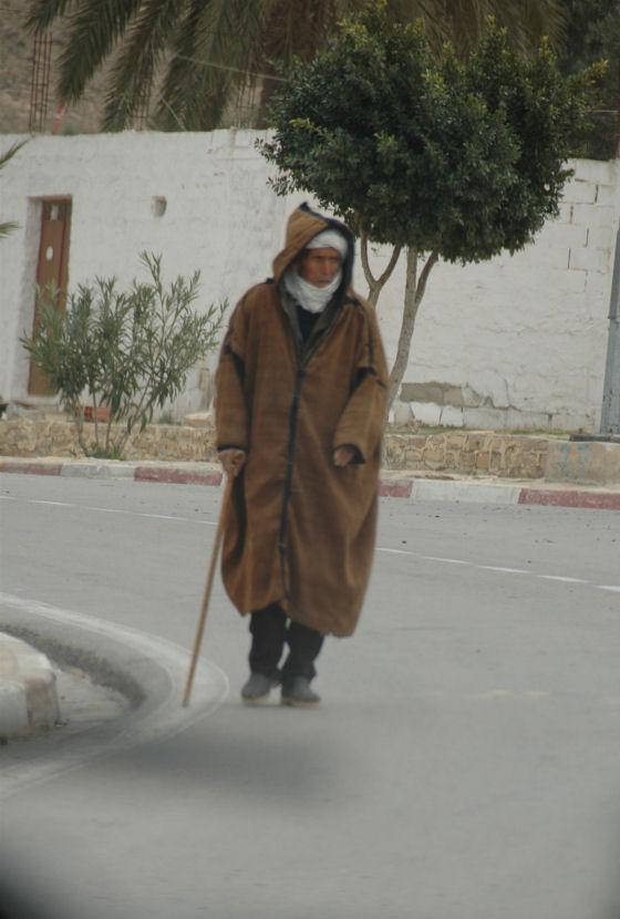 Zdjecie mieszkanca tunezji, ktory idzie ulica. Ubrany jest w zimową galabije, na glowie widac zawiazany turban, w reku trzyma jakąś drewnianą laskę.