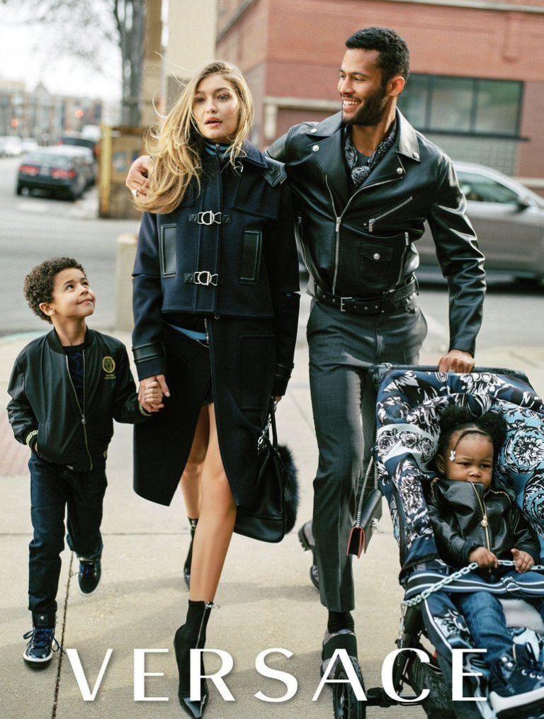 Fotografia reklamowa marki Versace. Na zdjęciu widać kobietę, blondynkę oraz czarnoskórego mężczyznę oraz dwójkę dzieci - jedno w wózku spacerowym.