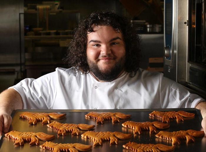 Uśmiechnięty mężczyzna kucający przed blachą z wypieczonymi ciastkami w kształcie wilków