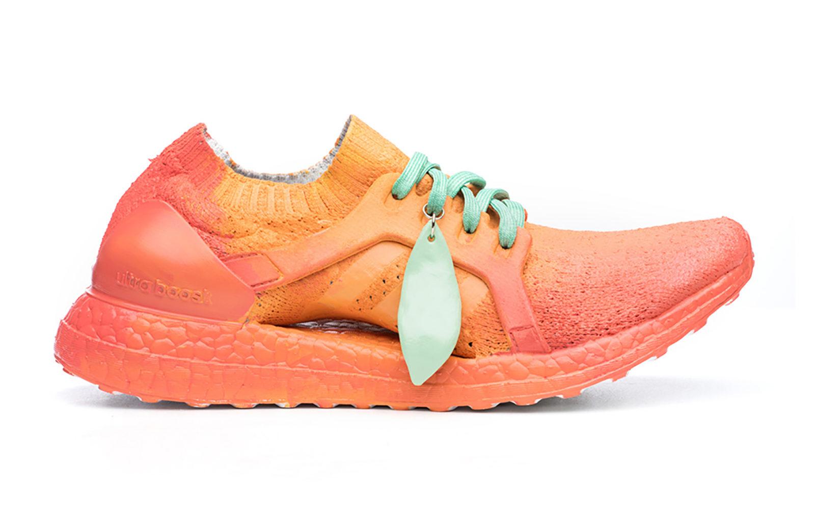 Fotografia reklamowa ukazując buty firmy Adidas, model Ultraboost w kolorze pomarańczowym, imitujące brzoskwinowe ciasto. z boku wisi zielony listek.