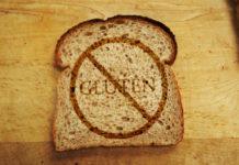 """Fotografia kolorowa. Na drewnianym stole leży kromka chleba na której widać przekreślony napis """"gluten"""" w kółku. W prawym górnym rogu również widać kawałki leżących kromek."""